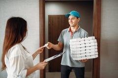 Le gar?on de livraison de pizza prend une astuce de client images stock