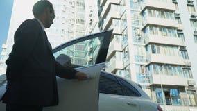 Le garde de sécurité ouvre les portières de voiture au patron de dame, sécurité pour le politicien, vue inférieure clips vidéos