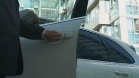 Le garde du corps ouvre la porte automatique au patron féminin, femme entrant dans le véhicule, sécurité banque de vidéos