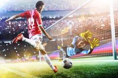 Le gardien de but attrape la boule sur le stade de football Image stock
