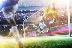 Le gardien de but attrape la boule sur le stade de football Photographie stock