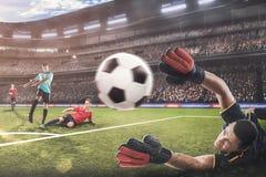 Le gardien de but sautant pour la boule sur le match de football image libre de droits