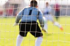 Le gardien de but a utilisé des mains pour des crochets la boule en match Image libre de droits