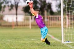 Le gardien de but a utilisé des mains pour des crochets la boule en match Photo stock