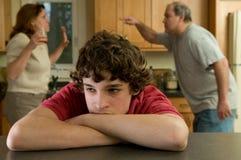 Le garçon (13-15) en douleur comme parents combattent à l'arrière-plan Photos libres de droits