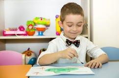 Le garçon adorable d'enfant dessine une brosse et des peintures dans la chambre de crèche Enfant dans le jardin d'enfants en clas Photos stock