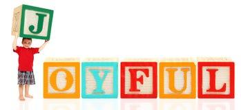 Le garçon avec l'alphabet bloque JOYEUX Photo stock