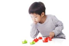 Le garçon concentré joue les bateaux de papier sur la table Images libres de droits