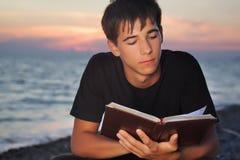 Le garçon d'adolescent affiche le livre se reposant sur la plage Images libres de droits