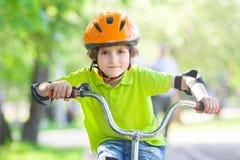 Le garçon dans un casque de sécurité monte une bicyclette Images stock