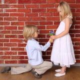 Le garçon donne à une fille des fleurs Photo libre de droits