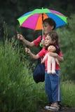 Le garçon et la fille sous le parapluie en stationnement déchirent l'herbe Image libre de droits