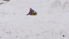 Le garçon glisse vers le bas la montagne dans la neige banque de vidéos