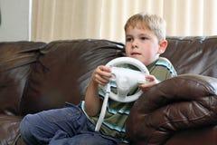 Le garçon joue le jeu vidéo Images stock