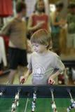Le garçon joyeux joue au football de table Photo libre de droits