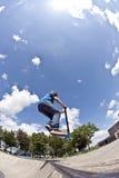 Le garçon a l'amusement avec le scooter dans le parc de patin Photo libre de droits