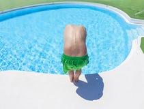Le garçon a l'amusement sautant dans la piscine extérieure Photos stock