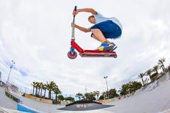 Le garçon monte son scooter à un parc de patin Image libre de droits
