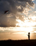 Le garçon pilote le cerf-volant. Photo libre de droits