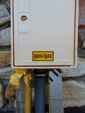 Le gaz jaune se connectent le boîtier blanc de la maison photographie stock