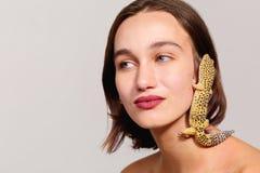 Le gecko d'iguane rampe à travers le visage d'une jeune brune sur un fond gris images stock