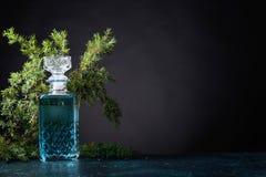 Le genièvre bleu dans le décanteur en cristal et le genévrier s'embranchent avec des baies photo libre de droits