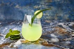 Le genièvre et le tonique en bon état de scintillement de concombre sifflent avec l'aloès Vera sur la table de marbre Copiez l'es images stock