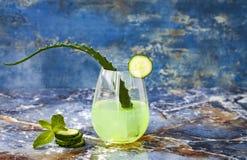 Le genièvre et le tonique en bon état de scintillement de concombre sifflent avec l'aloès Vera sur la table de marbre Copiez l'es image stock
