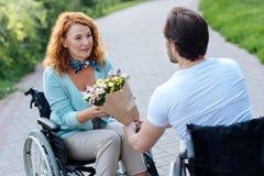 Le gentil aîné wheelchaired la femme obtenant un groupe de fleurs Photographie stock
