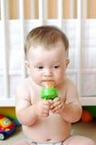 Le gentil bébé mange à l'aide du grignoteur Photos stock