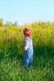 Le gentil enfant dans la combinaison de jeans et le bandana rouge plument des fleurs Photographie stock