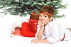 Le gentil garçon se trouve sous l'arbre de Noël images stock