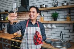 Le gentil homme adulte dans le support de tablier seul et regardent le verre dans la cuisine Il brillent avec le cleaness Serviet photographie stock