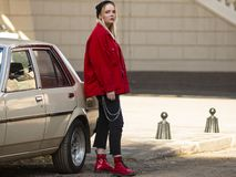 Le gentil jeune hippie blond se tient près de la vieille voiture sur la rue images libres de droits