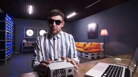 Le gentil jeune mâle semblant parle à la boîte de participation de caméra d'alimentation d'énergie avec le refroidisseur clips vidéos