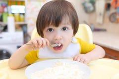 Le gentil petit enfant mange le quark Photographie stock libre de droits