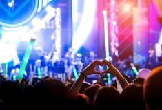 Le geste de main aime le doigt aux lumières d'étape de concert Images stock