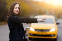 Le geste de main de femme de brune attrape le taxi Looking modèle à l'appareil-photo photographie stock