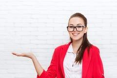Le geste de main ouvert de paume de femme d'affaires aux verres rouges de veste d'usage de l'espace de copie sourient Photographie stock libre de droits