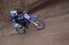 Le gestionnaire d'emballage de motocyclette conduit dans une montée escarpée Photo stock