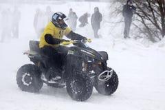 Le gestionnaire du vélo de quarte conduit au-dessus de la piste de neige Images libres de droits