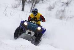 Le gestionnaire du vélo de quarte conduit au-dessus de la piste de neige Photo libre de droits