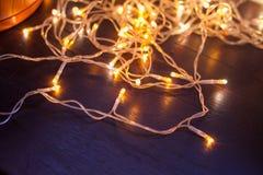Le ghirlande brillanti di Natale su un fondo di legno Fotografia Stock Libera da Diritti