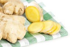 Le gingembre coupé en tranches s'enracine sur la serviette à carreaux verte Photos stock
