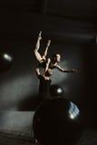 Le ginnaste concentrate che ballano insieme nel nero hanno colorato lo studio Fotografia Stock Libera da Diritti