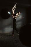 Le ginnaste imperiose che ballano insieme nel nero hanno colorato lo studio Immagine Stock