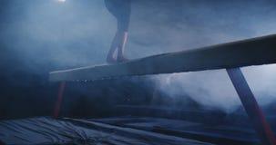 Le ginnaste professionisti della ragazza delle gambe saltano al rallentatore nel fumo sul fascio di equilibrio La ginnastica arti stock footage