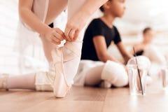 Le giovani ballerine riposano durante un irrompere che il balletto classifica Fotografia Stock