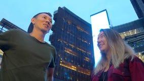 Le giovani bei coppie, tipo e ragazza asiatici stanno parlando a vicenda, stando sulla via della città video d archivio