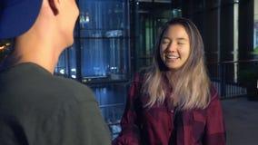 Le giovani bei coppie, tipo e ragazza asiatici stanno parlando a vicenda, stando sulla via della città stock footage